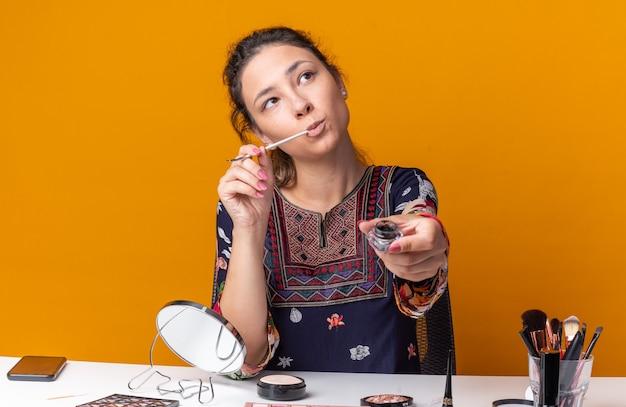 Premurosa giovane ragazza bruna seduta al tavolo con strumenti per il trucco che tiene eyeliner e tavolozza di ombretti guardando in alto isolato sulla parete arancione con spazio di copia