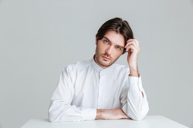 회색 벽에 격리된 테이블에 앉아 있는 흰색 셔츠를 입은 사려 깊은 젊은 브루네트 남자