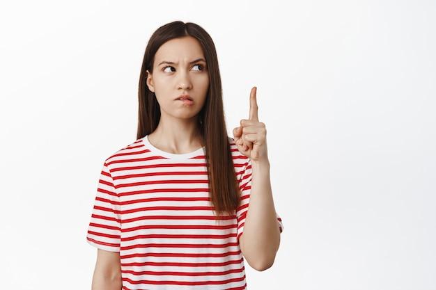 Premurosa giovane donna bruna che punta verso l'alto, guardando da parte il banner di vendita e pensando, meditare su qualcosa di interessante, avere un'idea, in piedi sul muro bianco.