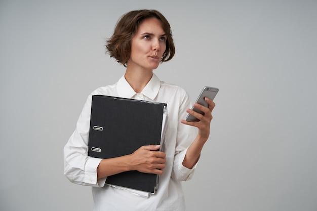 Задумчивая молодая брюнетка с повседневной прической держит мобильный телефон в руке и задумчиво смотрит в сторону, назначает встречу в рабочий день, позирует над белой офисной стеной