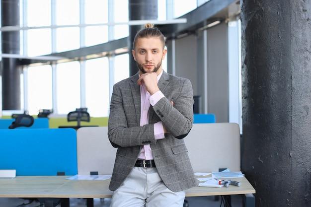 カメラを見て、机に寄りかかっている間あごに手を置いてカジュアルな服を着た思いやりのある若いビジネスマン。