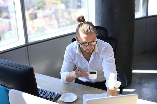 Вдумчивый молодой деловой человек в рубашке работает с помощью компьютера и пьет кофе, сидя в офисе.