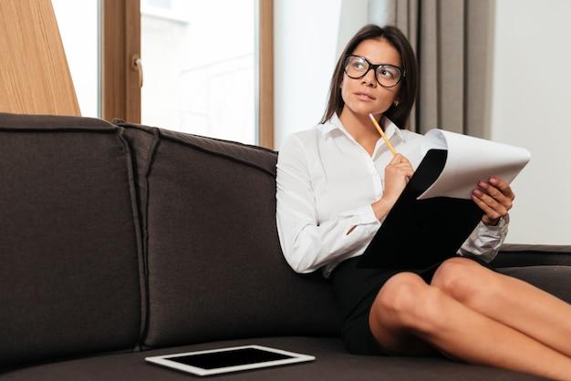 仕事をしながらメモを取る思いやりのある若いビジネス女性