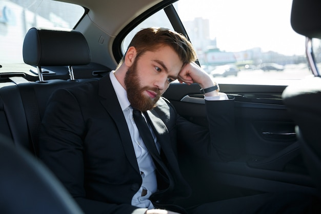 Thoughtful young businessman holding hand on forehead and looking away