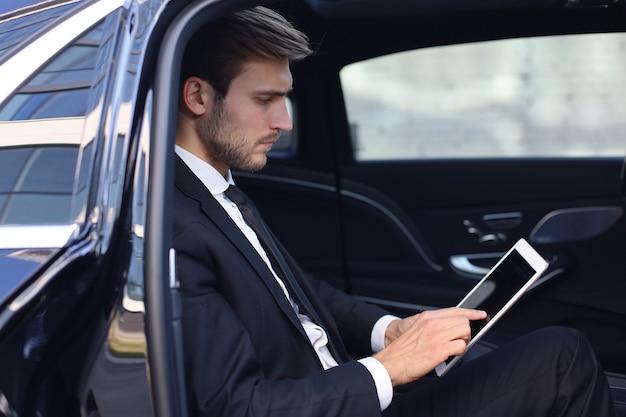 사려깊은 젊은 사업가가 고급 차에 앉아 태블릿을 사용합니다.