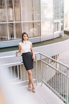 Giovane donna di affari premurosa che tiene la tazza di caffè asportabile che sta nel balcone
