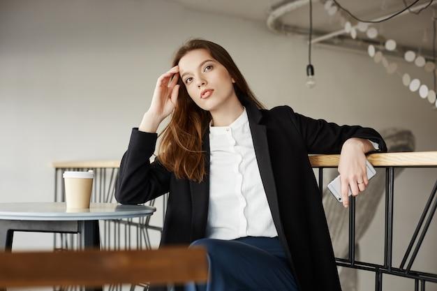 思いやりのある若い実業家座っているカフェ、夢のようなよそ見