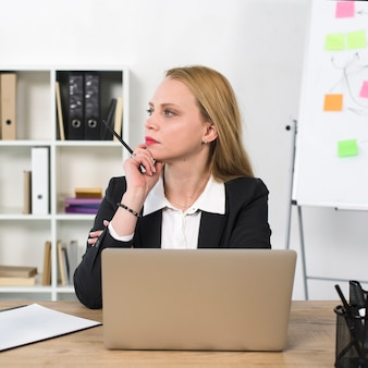 Thoughtful young businesswoman sitting at workplace with laptop on table