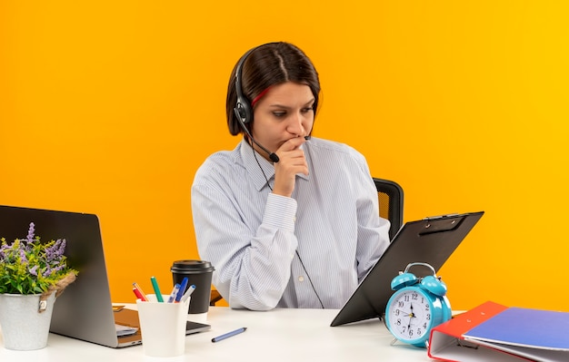 Giovane ragazza premurosa del call center che indossa la cuffia avricolare che si siede allo scrittorio con gli strumenti di lavoro che mettono la mano sul mento che esamina la lavagna per appunti isolata sulla parete arancione