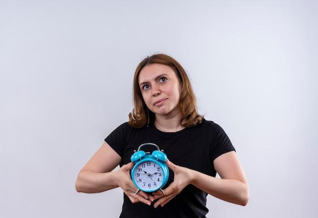 目覚まし時計を保持し、コピースペースのある孤立した白い壁を見上げる思いやりのある若いカジュアルな女性
