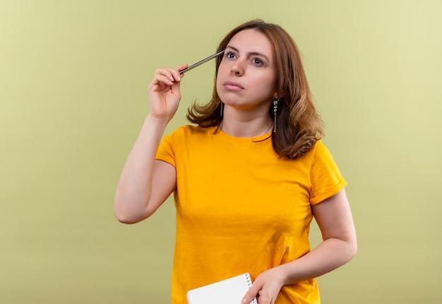 Giovane donna casuale premurosa che tiene la penna e il blocco note sulla parete verde isolata con lo spazio della copia