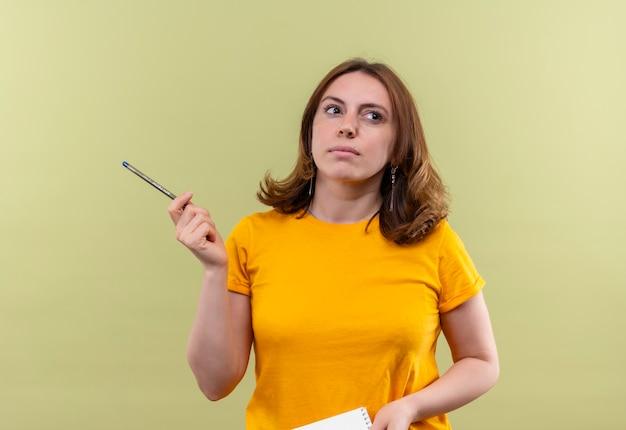 Giovane donna casuale premurosa che tiene la penna e il blocco note sulla parete verde isolata