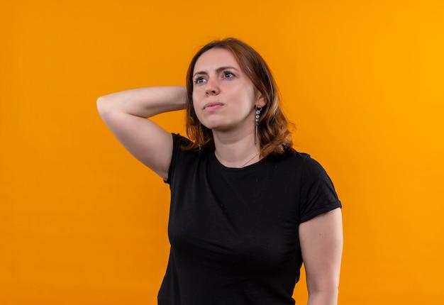 孤立したオレンジ色の壁に頭の後ろに手を置く思いやりのある若いカジュアルな女性