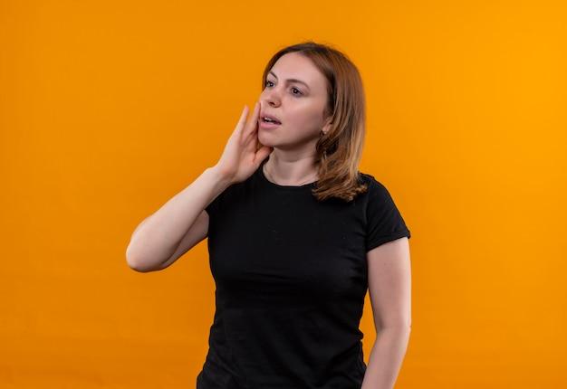 コピースペースと孤立したオレンジ色の壁に頬に手を置く思いやりのある若いカジュアルな女性