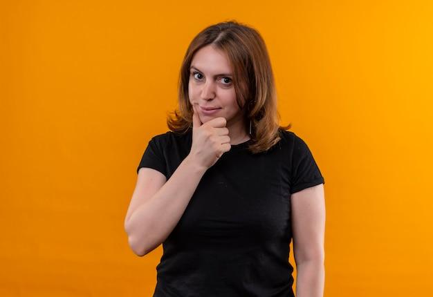 コピースペースと孤立したオレンジ色の壁のあごに手を置く思いやりのある若いカジュアルな女性