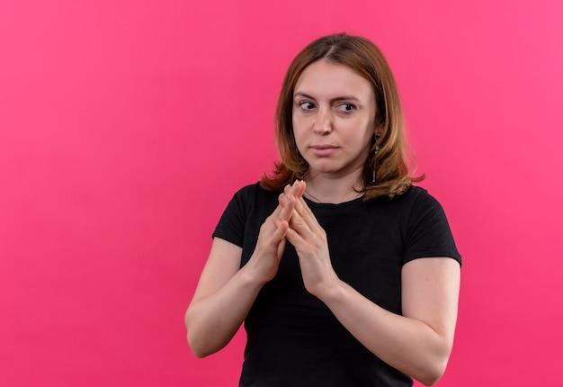 コピースペースと孤立したピンクの壁に手を一緒に置く思いやりのある若いカジュアルな女性