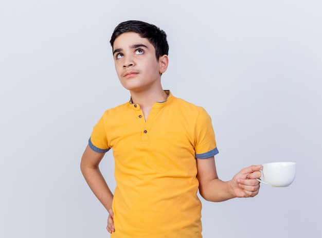 Thoughtful young caucasian boy holding cup keeping hand on waist looking up isolated on white background