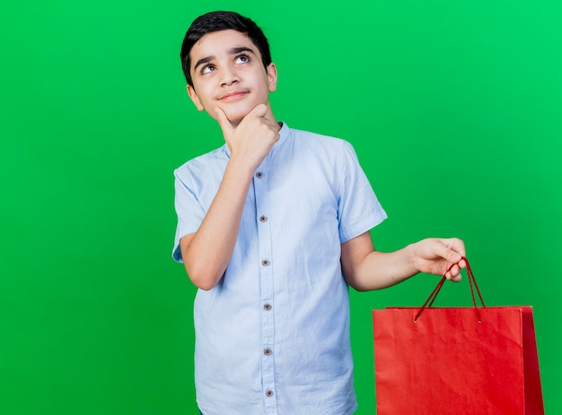 Giovane ragazzo caucasico premuroso che tiene il sacchetto della spesa che tocca il mento che esamina lato isolato sulla parete verde con lo spazio della copia