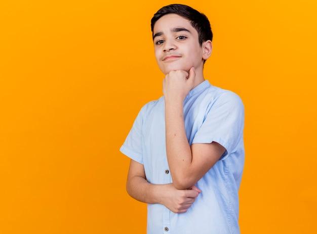 思いやりのある若い白人の少年は、コピースペースとオレンジ色の背景に分離された下を見下ろしているあごの下に手を置く