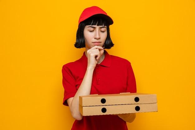 피자 상자를 들고 보고 있는 사려깊은 젊은 백인 배달 소녀