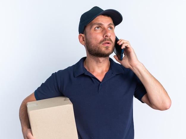 Giovane uomo caucasico premuroso di consegna in uniforme blu e cappuccio che tiene scatola di cartone che guarda in su parlando al telefono