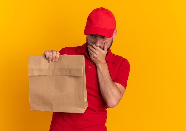 Giovane fattorino caucasico premuroso in uniforme rossa e cappuccio che tiene il pacchetto di carta tenendo la mano sulla bocca guardando in basso