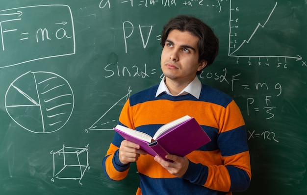 Thoughtful young caucasian geometry teacher standing in front of chalkboard in classroom holding book looking up