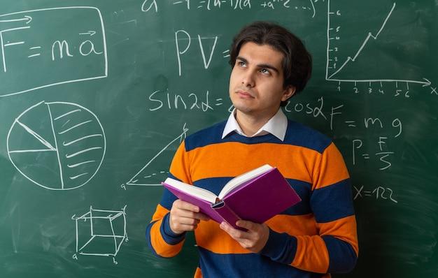 Задумчивый молодой учитель кавказской геометрии, стоящий перед классной доской в классе, держа книгу, глядя вверх