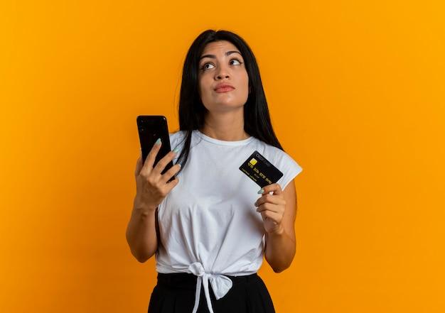La giovane ragazza caucasica premurosa tiene il telefono e la carta di credito che esaminano lato