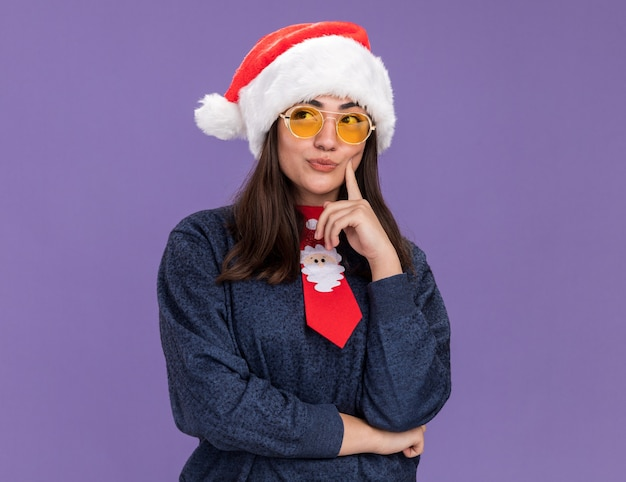 산타 모자와 산타 넥타이와 태양 안경에 사려 깊은 젊은 백인 여자는 얼굴에 손가락을 넣고 복사 공간이 보라색 벽에 고립 된 측면에서 보인다
