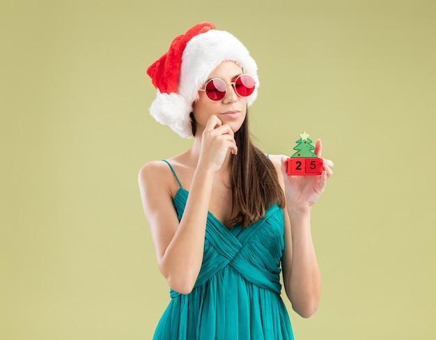 산타 모자와 태양 안경에 사려 깊은 젊은 백인 여자는 턱을 잡고 크리스마스 트리 장식을보고 손을 넣습니다