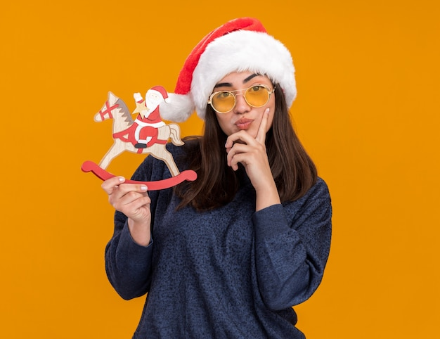 Thoughtful young caucasian girl in sun glasses with santa hat puts finger on chin and holds santa on rocking horse decoration isolated on orange background with copy space