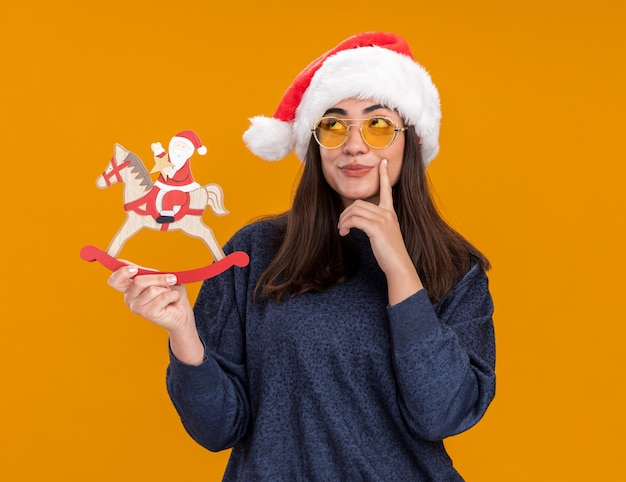 Thoughtful young caucasian girl in sun glasses with santa hat puts finger on chin and holds santa on rocking horse decoration looking up isolated on orange wall with copy space