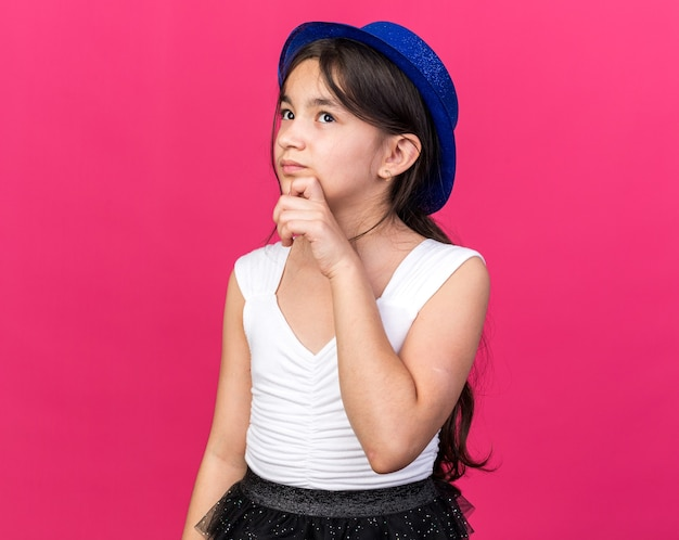 Thoughtful young caucasian girl with blue party hat holding chin and looking up isolated on pink wall with copy space