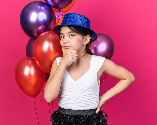 Thoughtful young caucasian girl with blue party hat holding chin standing in front of helium balloons looking up isolated on pink wall with copy space