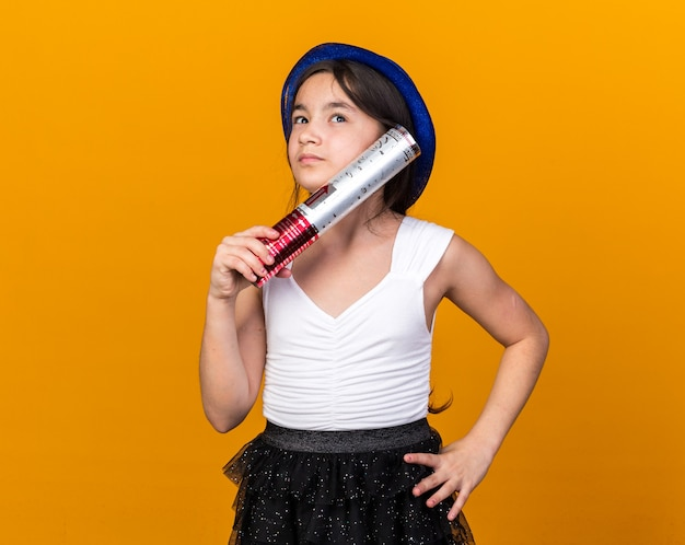 Thoughtful young caucasian girl with blue party hat holding confetti cannon and looking at side isolated on orange wall with copy space