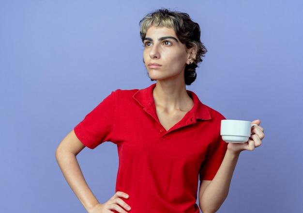 サイドを見て腰に手を置いてピクシー カットを保持しているカップを持つ思いやりのある若い白人の女の子