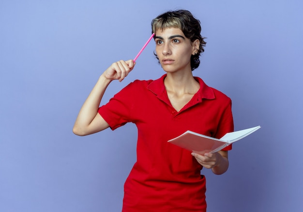 펜으로 이마를 만지고 복사 공간이 보라색 배경에 고립 된 측면을보고 펜과 노트 패드를 들고 픽시 머리와 사려 깊은 젊은 백인 여자