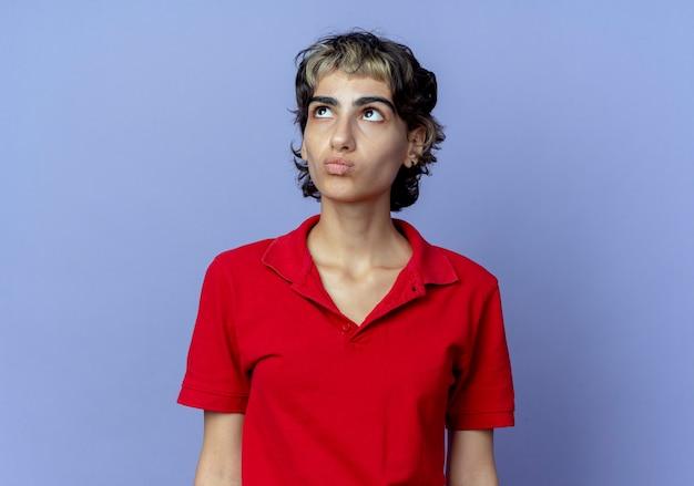 Riflessivo giovane ragazza caucasica con pixie haircut cercando isolato su sfondo viola con copia spazio