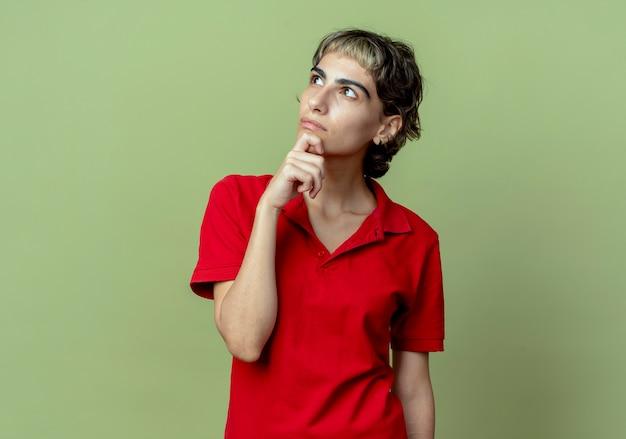 턱에 손을 넣어 픽시 머리와 사려 깊은 젊은 백인 여자는 복사 공간 올리브 녹색 배경에 고립 찾고