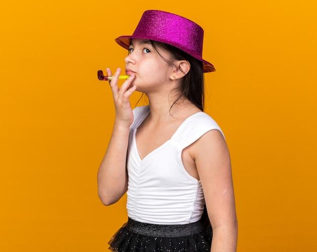 Вдумчивая молодая кавказская девушка в фиолетовой шляпе смотрит вверх, держа партийный свисток, изолированную на оранжевой стене с копией пространства