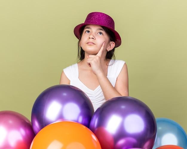 Premurosa giovane ragazza caucasica con cappello da festa viola che mette la mano sul mento e alza lo sguardo in piedi con palloncini di elio isolati su parete verde oliva con spazio di copia