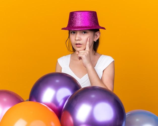 あごに手を置き、コピースペースとオレンジ色の壁に分離されたヘリウム風船で立っている紫色のパーティハットを持つ思いやりのある若い白人の女の子
