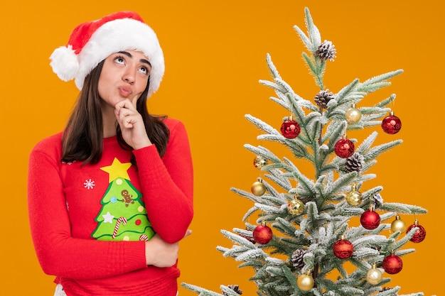 산타 모자와 사려 깊은 젊은 백인 여자는 복사 공간 오렌지 배경에 고립 된 크리스마스 트리 옆에 서 찾고 턱을 보유