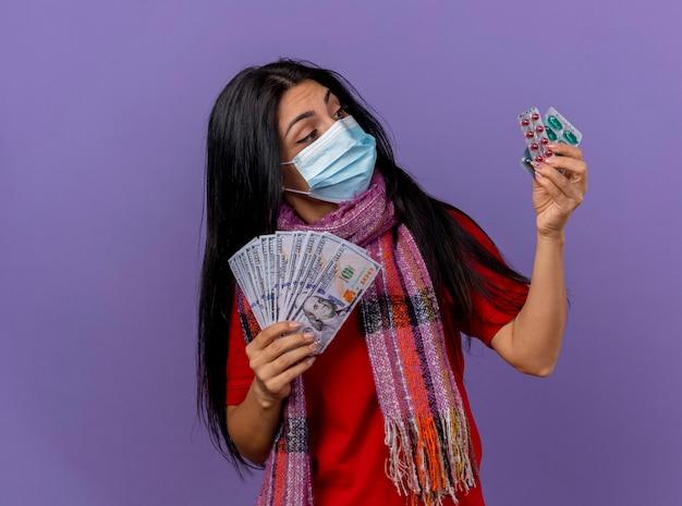 Riflessivo giovane ragazza malata caucasica indossando maschera e sciarpa tenendo i soldi e il pacchetto di capsule guardando le capsule isolate sulla parete viola con lo spazio della copia