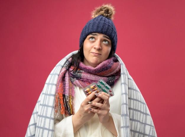 真っ赤な壁に孤立して見上げるカプセルの格子縞の保持パックに包まれたローブの冬の帽子とスカーフを身に着けている思いやりのある若い白人の病気の女の子