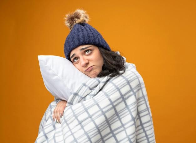 Задумчивая молодая кавказская больная девушка в зимней шапке, завернутой в плед, стоя в профиль, обнимая подушку, глядя вверх, изолированные на оранжевом фоне