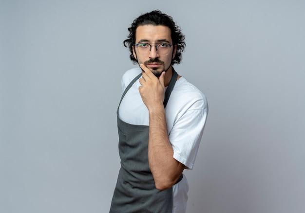 Вдумчивый молодой кавказский мужчина-парикмахер в очках и волнистой повязке для волос в униформе трогательно подбородок изолирован на белом фоне с копией пространства