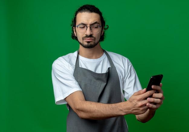 Вдумчивый молодой кавказский мужчина-парикмахер в униформе и очках держит и смотрит на мобильный телефон, изолированный на зеленом фоне с копией пространства