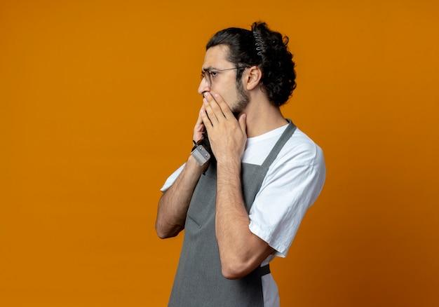 Riflessivo giovane maschio caucasico barbiere che indossa l'uniforme e gli occhiali in piedi in vista di profilo guardando dritto tenendo le tosatrici e tenendo la mano sulla bocca